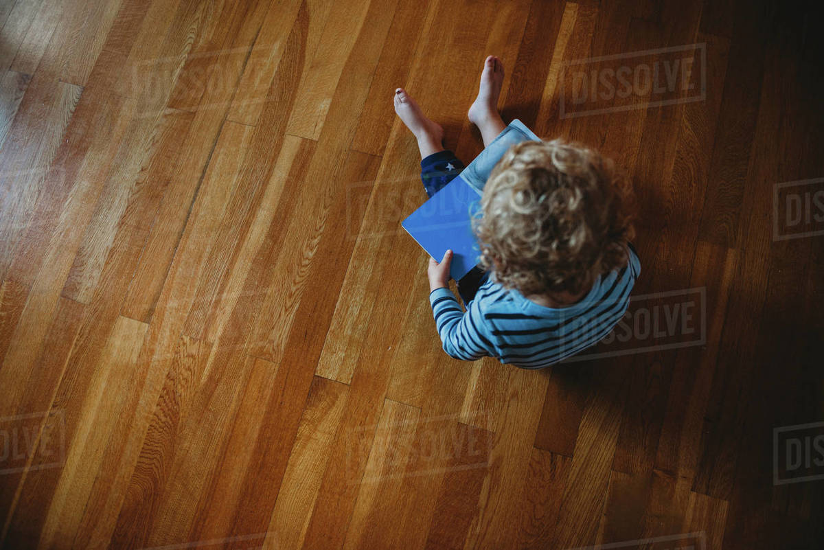 Top view of a young child with curls reading a book on the floor Royalty-free stock photo