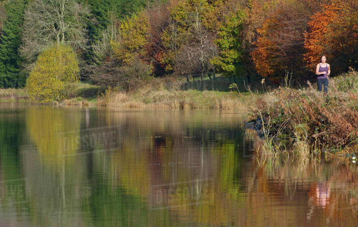 Woman running by still lake in south Wales Royalty-free stock photo