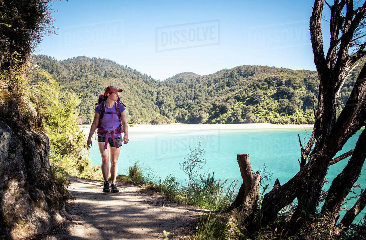Woman walking on trail with backpack with ocean behind her Royalty-free stock photo