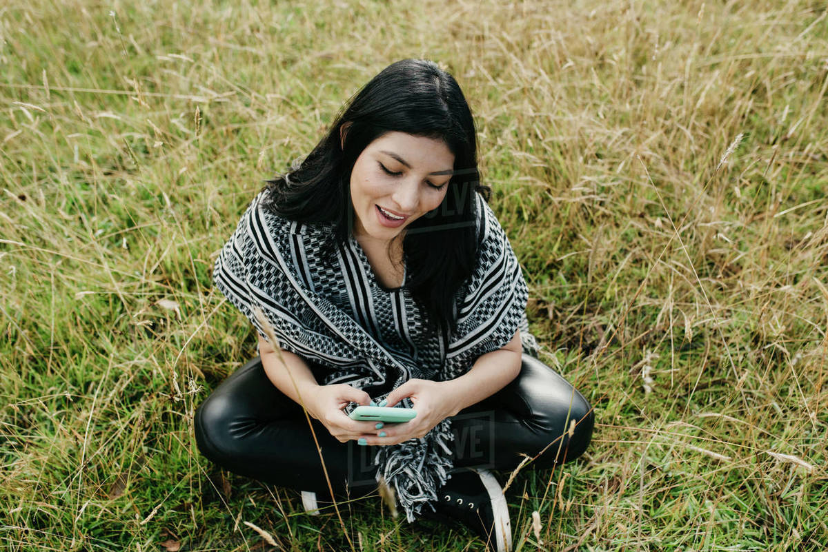 Portrait of a cute hispanic woman in the park writing on the phone Royalty-free stock photo