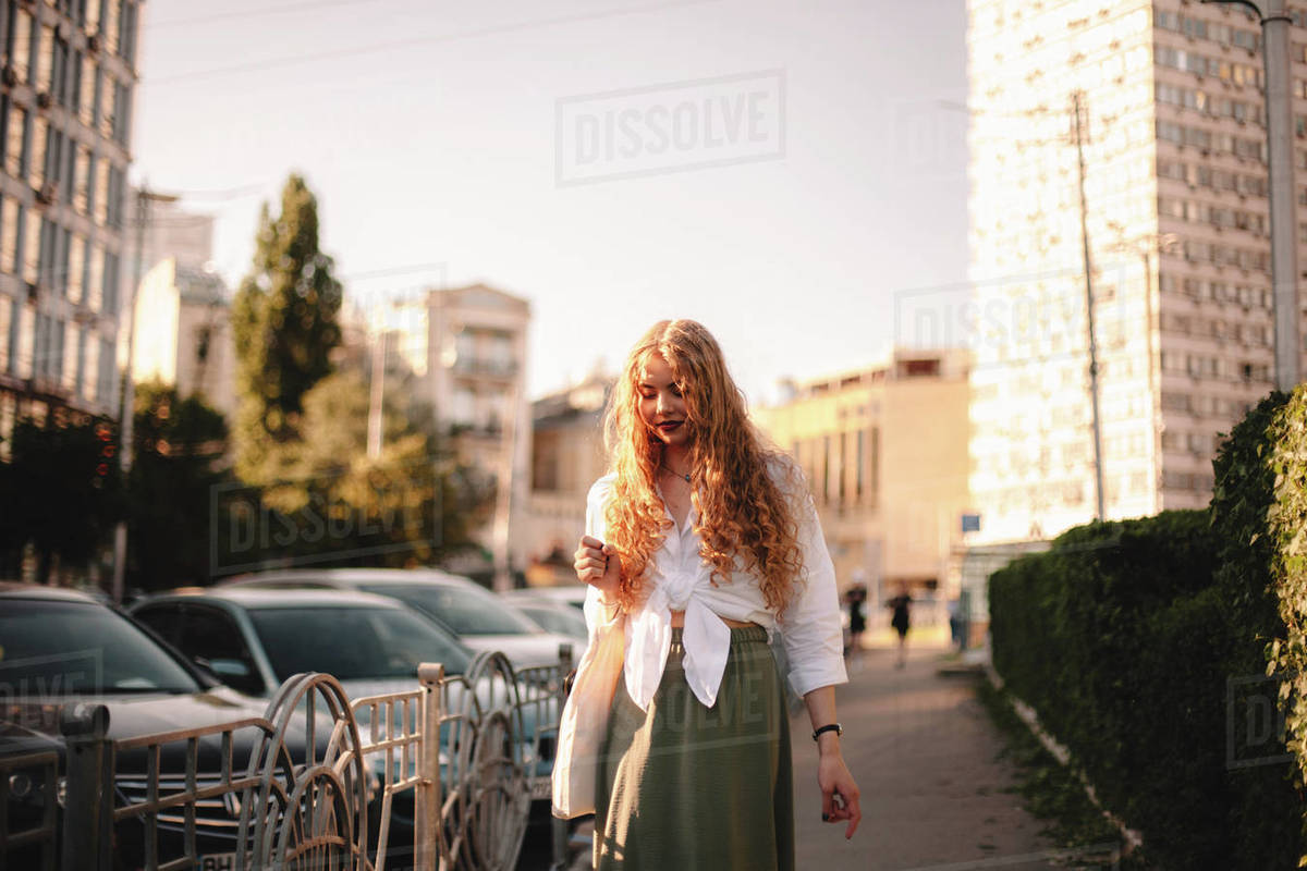 Thoughtful young woman walking on sidewalk in city during summer Royalty-free stock photo