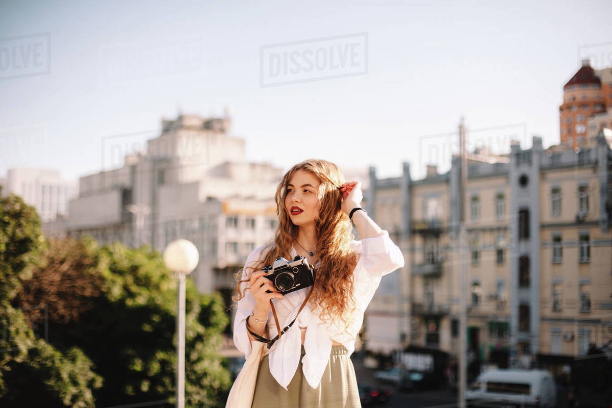 Thoughtful young woman holding camera while standing in city in summer Royalty-free stock photo