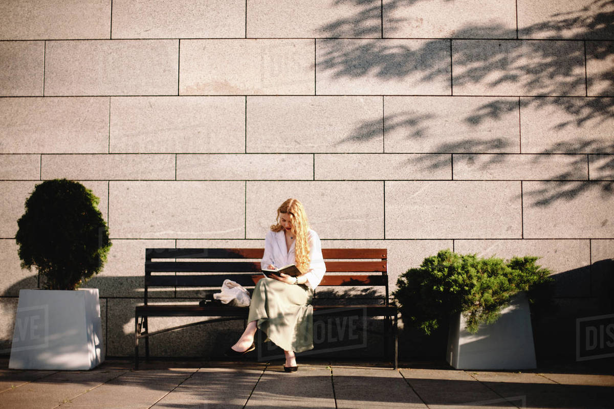 Young woman writing in diary sitting on bench by wall in summer city Royalty-free stock photo