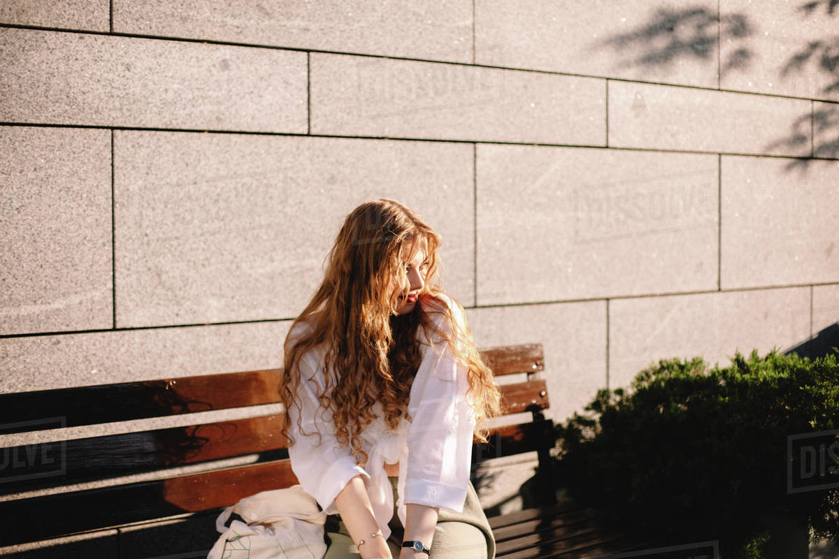 Portrait of young woman sitting on bench by wall in city in summer Royalty-free stock photo