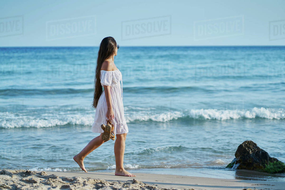 Young woman wearing sunglasses and wearing a white dress Royalty-free stock photo