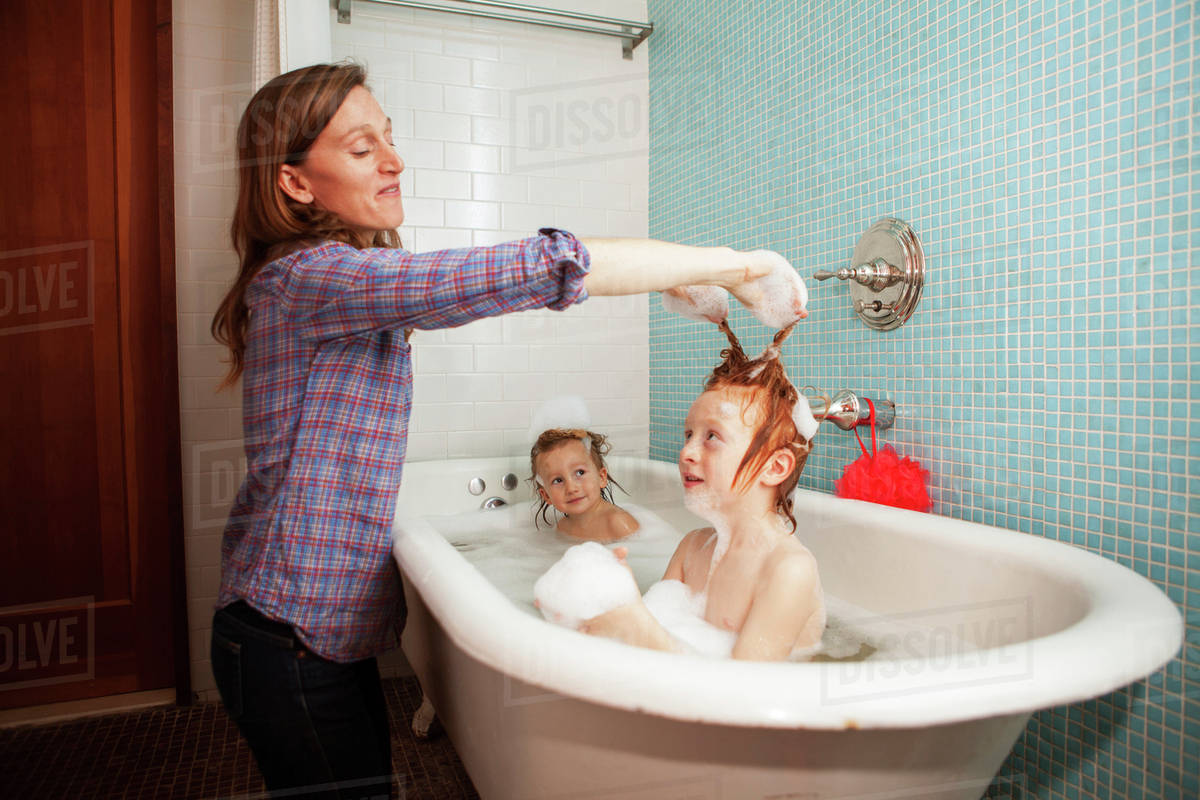 Mother bathing her son and daughter in bathtub - Stock Photo - Dissolve