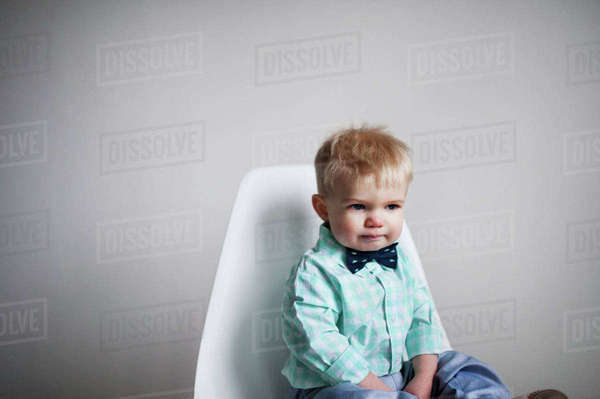 Sad baby boy sitting on chair against white wall at home Royalty-free stock photo