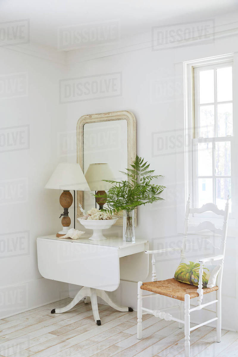 Decorated Table And Mirror By Window In Beach Cottage