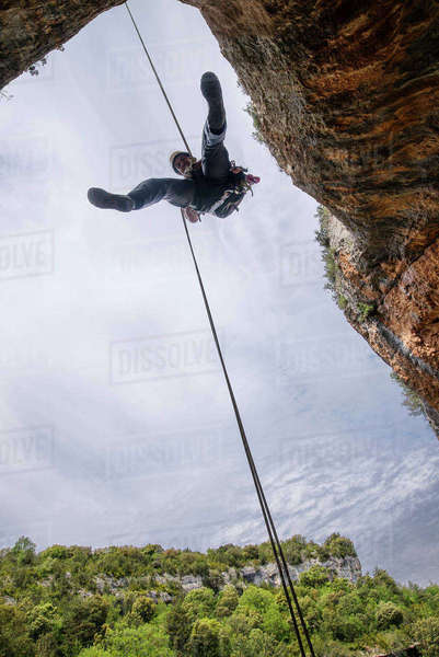 Low angle view of man rappelling from mountain against sky Royalty-free stock photo