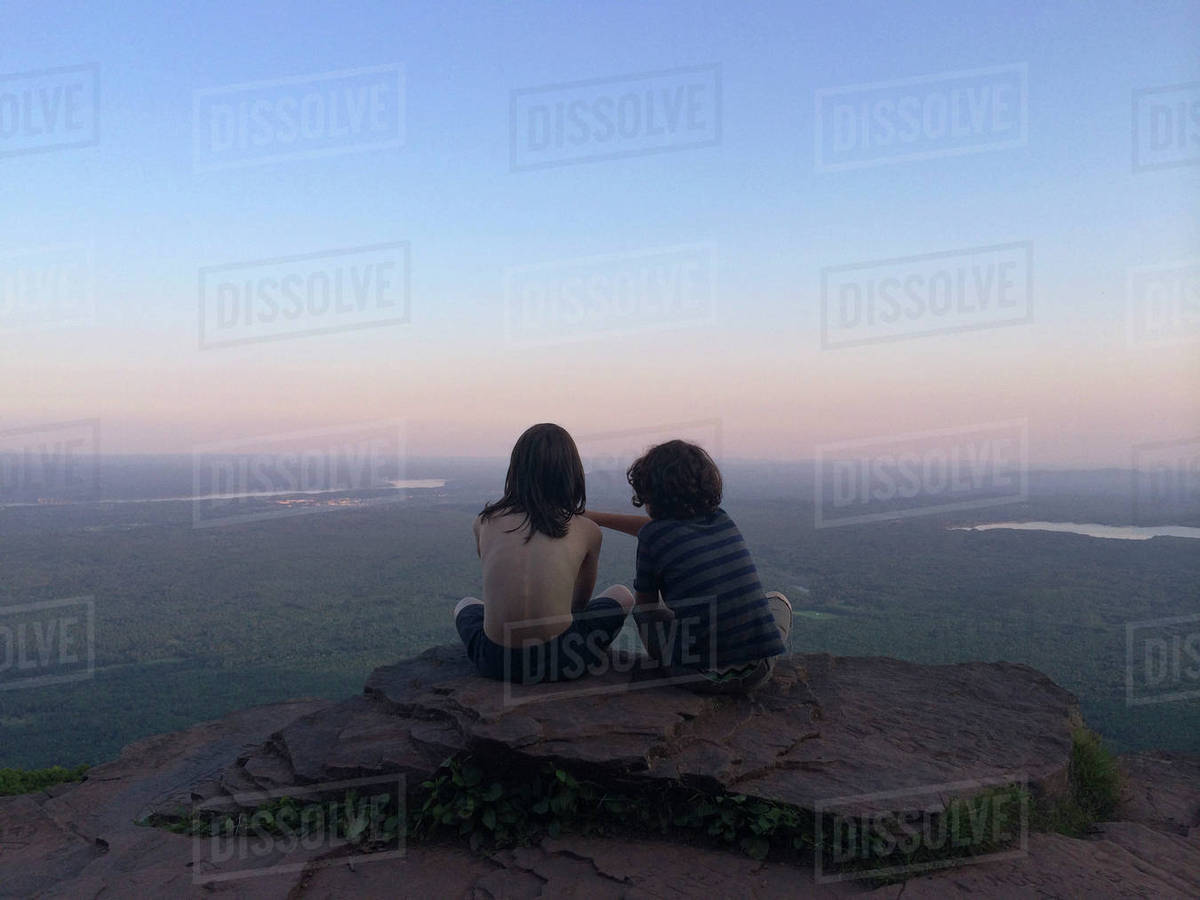 Rear view of friends sitting on cliff surrounded by landscape against sky Royalty-free stock photo