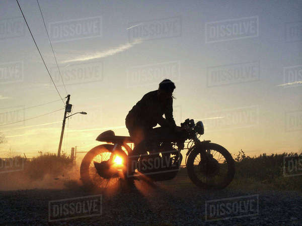Silhouette of man riding motorcycle against sky Royalty-free stock photo