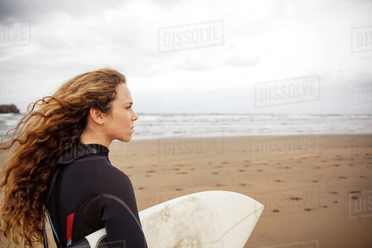 Side view of woman carrying surfboard at beach Royalty-free stock photo