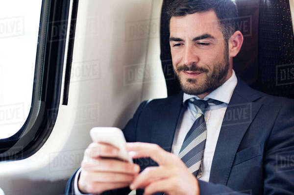 Businessman using smart phone in train Royalty-free stock photo