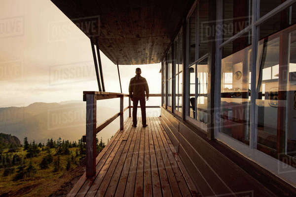 Rear view of man standing on balcony of cottage against sky Royalty-free stock photo