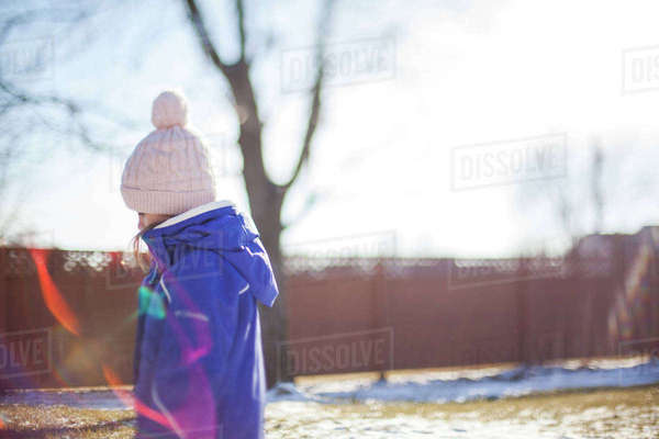 Side view of girl wearing knit hat standing in yard on sunny day during winter Royalty-free stock photo