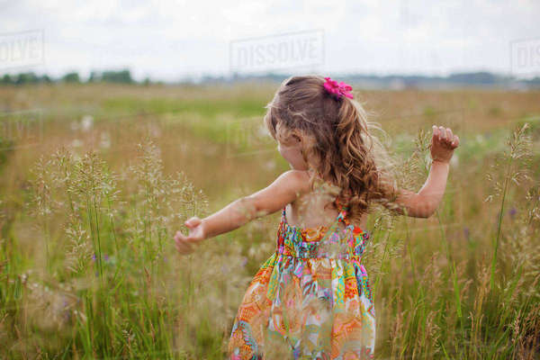 Girl with arms outstretched playing on grassy field Royalty-free stock photo