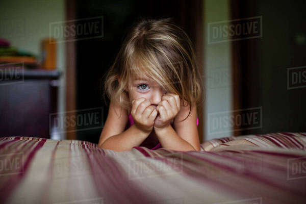 Portrait of cute girl leaning on bed at home Royalty-free stock photo