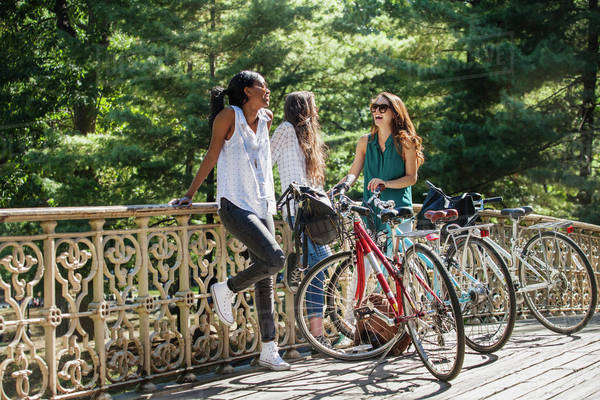 Female friends standing on bridge with bicycles Royalty-free stock photo