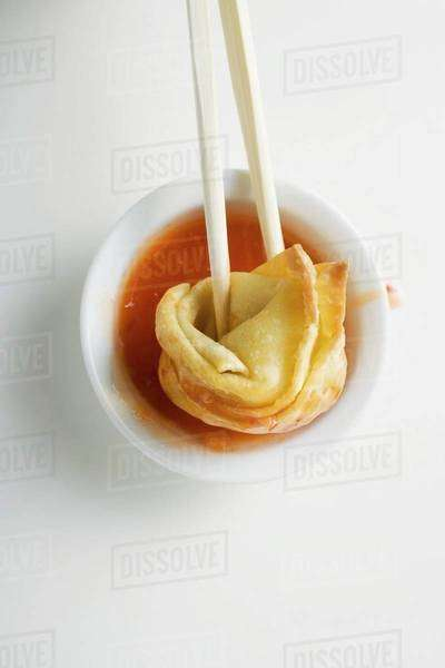 Dipping a deep-fried wonton in sweet and sour sauce Royalty-free stock photo