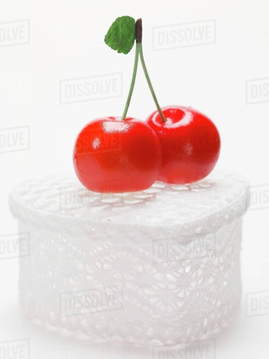 Marzipan cherries on heart-shaped gift box & Marzipan cherries on heart-shaped gift box - Stock Photo - Dissolve