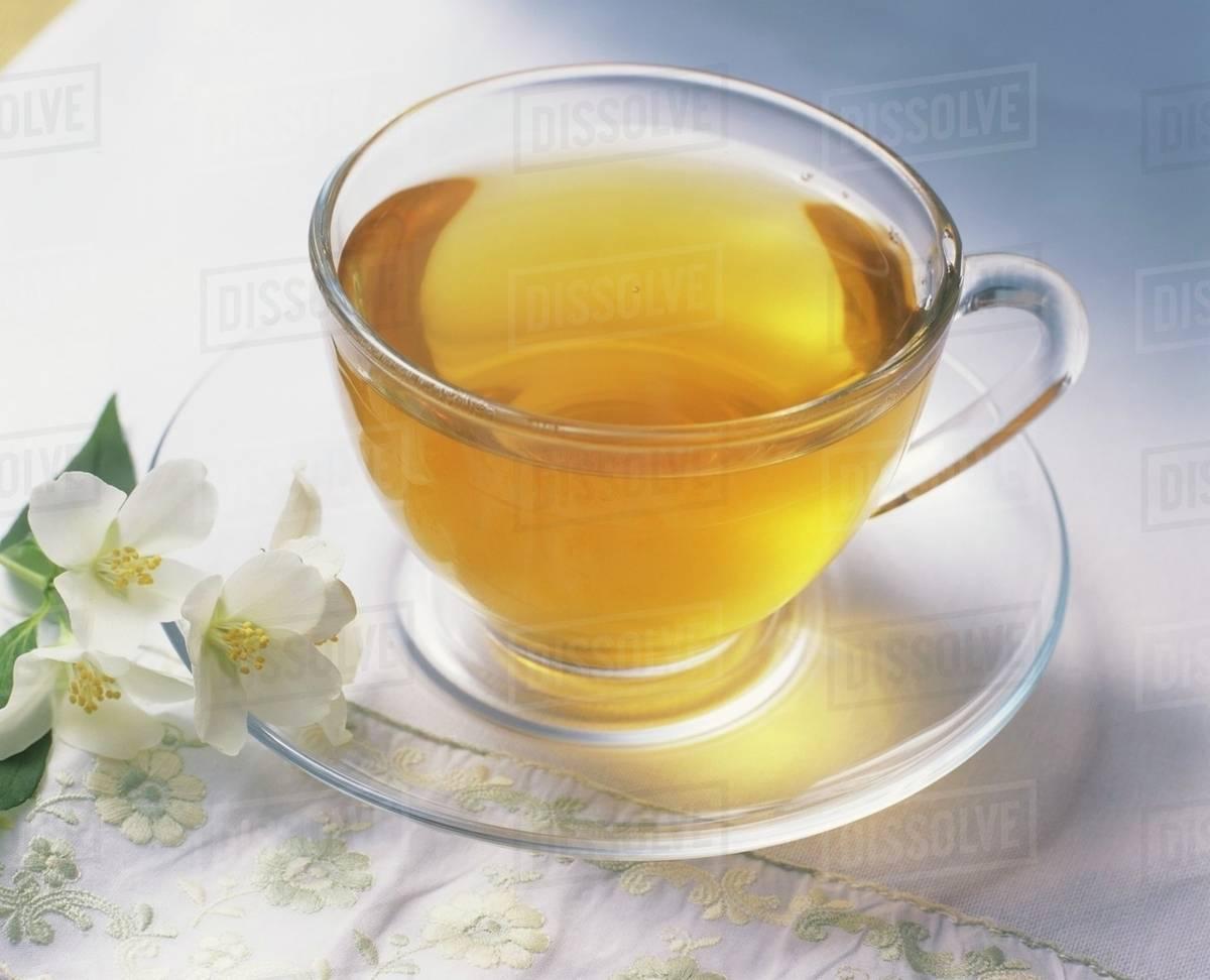 A Cup Of Green Tea Jasmine Flowers Beside It Stock Photo Dissolve