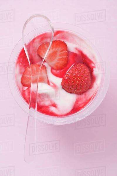 Strawberry yoghurt in plastic pot with spoon (overhead view) Royalty-free stock photo