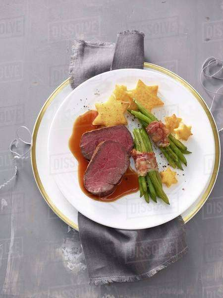 Beef fillet with polenta stars and beans wrapped in bacon Royalty-free stock photo