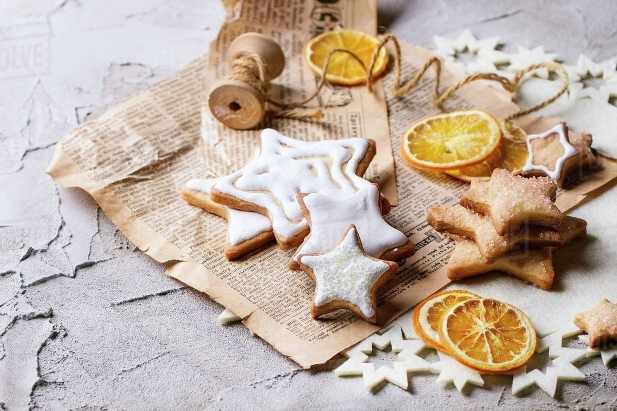 Glazed Christmas Star Biscuits And Dried Orange Slices On An Old Newspaper Stock Photo