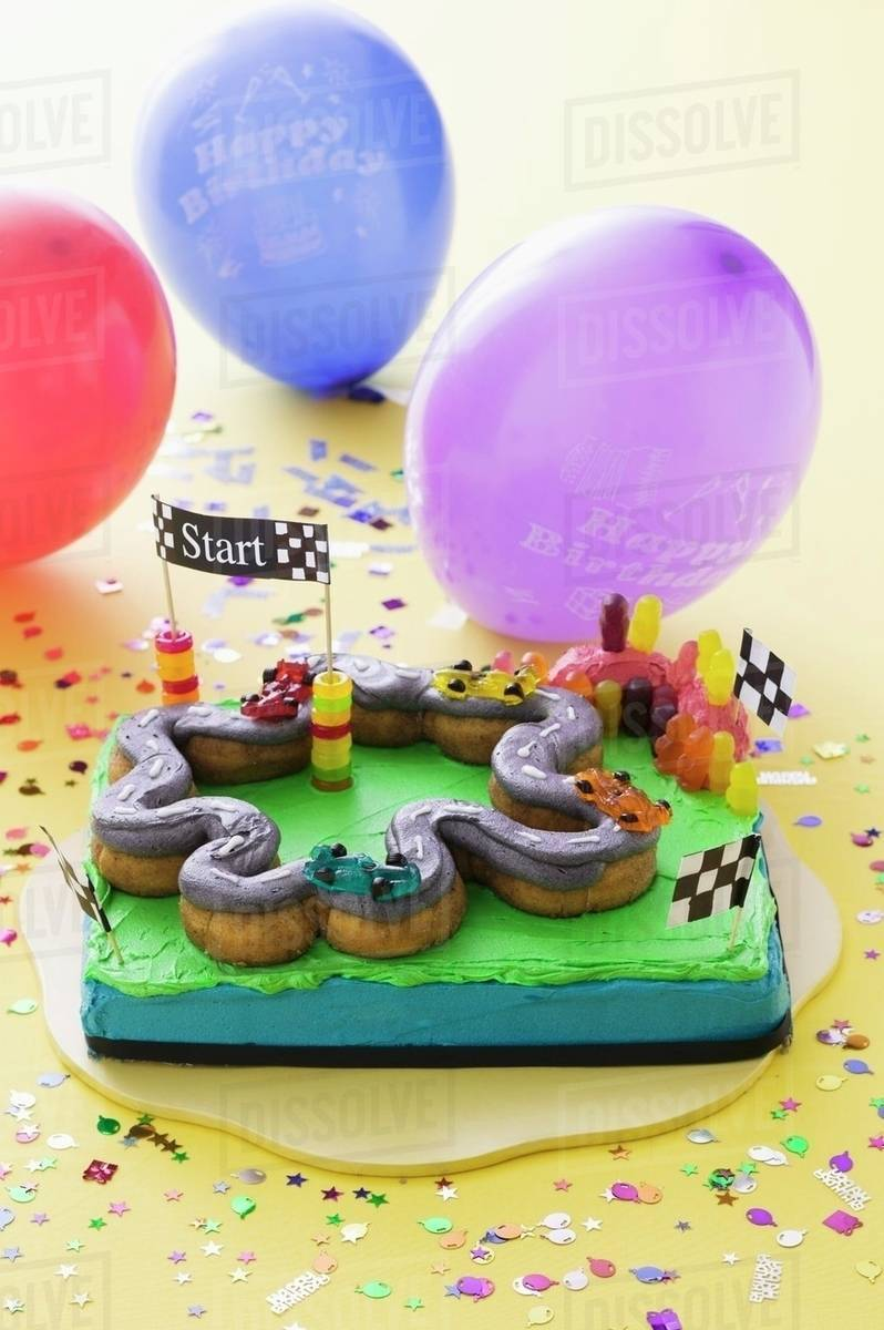 A Childs Birthday Cake Racing Track And Balloons