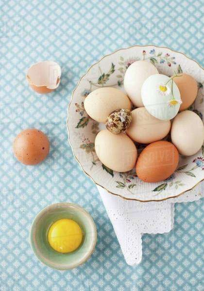 A Variety of Eggs in a Bowl with a White and Yellow Flower; From Above; One Egg Cracked Open Royalty-free stock photo
