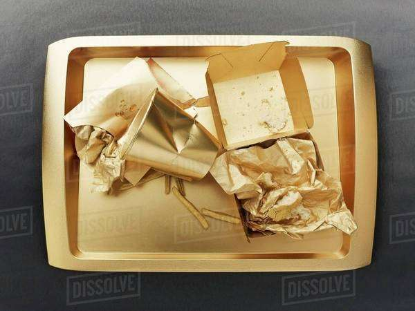 The remains of a fast food meal on a gold-coloured tray Royalty-free stock photo