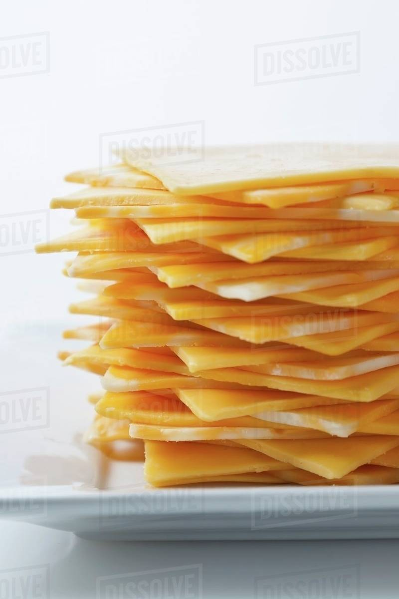 Stack of yellow American and Colby jack cheese on a white plate stock photo