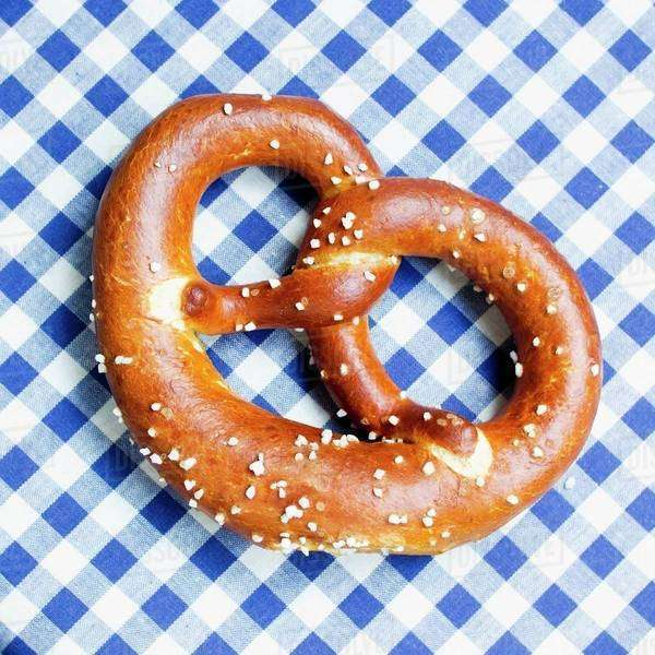 A pretzel on a blue and white tablecloth Royalty-free stock photo