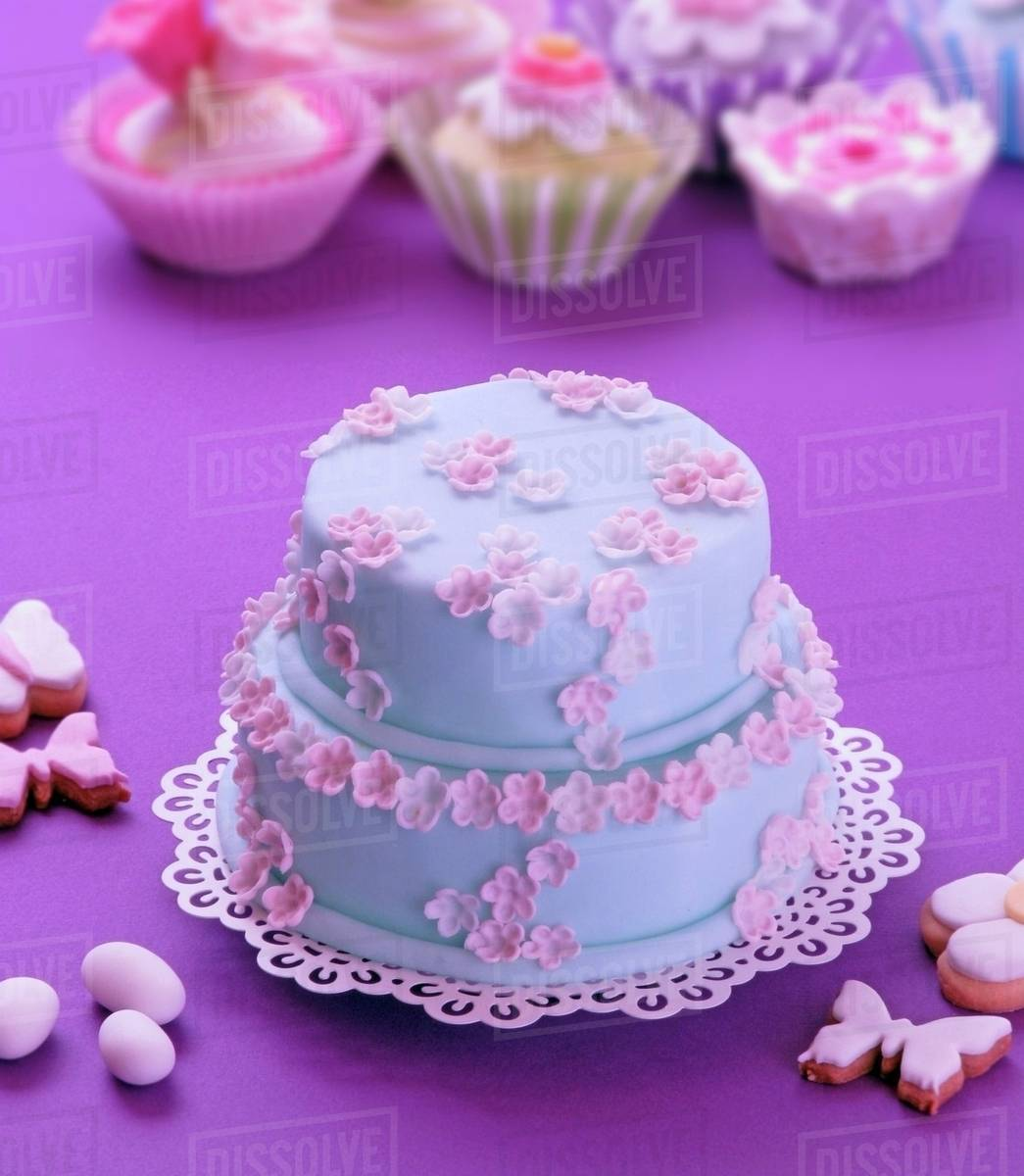 A Two Tier Easter Cake Decorated With Blue Icing And Pink Sugar