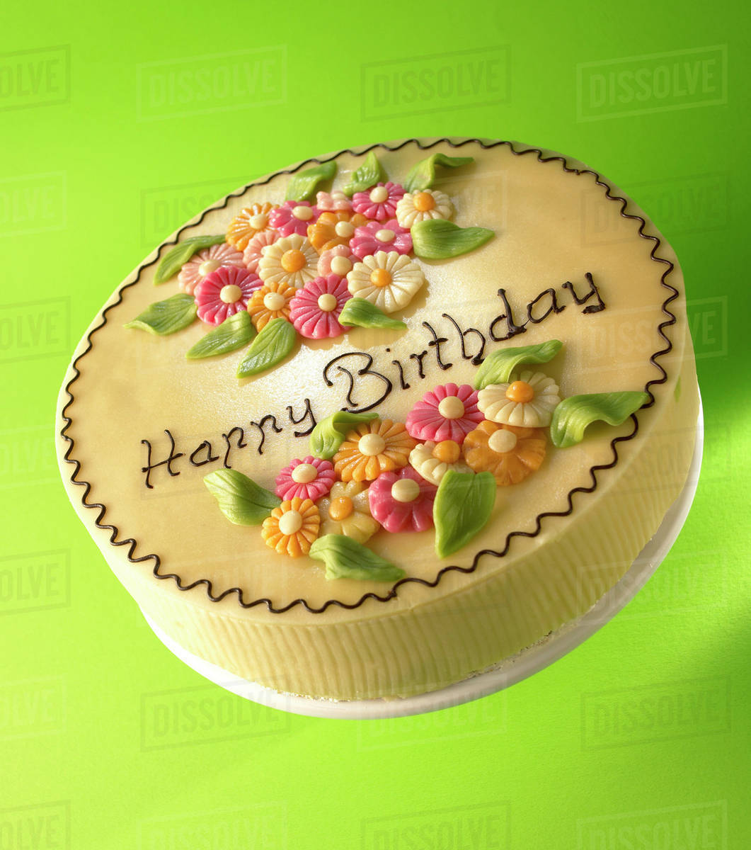 Cake With Marzipan Flowers And The Words Happy Birthday