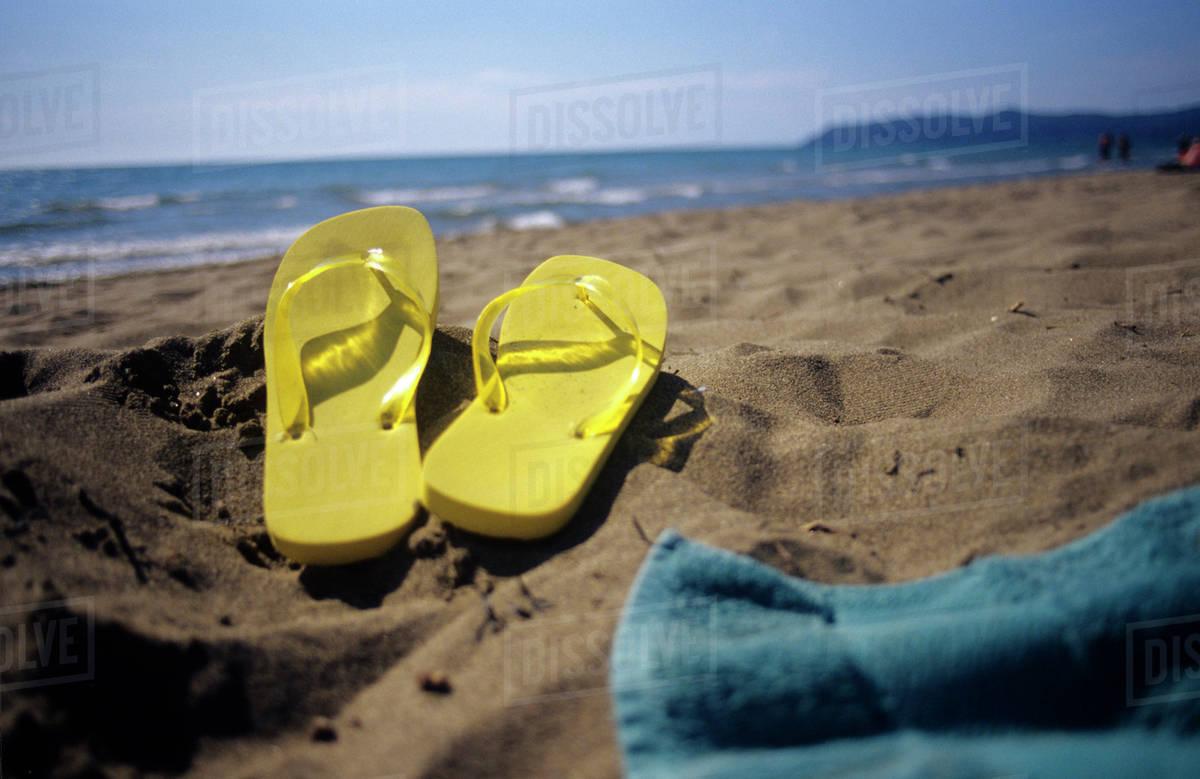 e3e85b01e Flip flops on sand at beach - Stock Photo - Dissolve