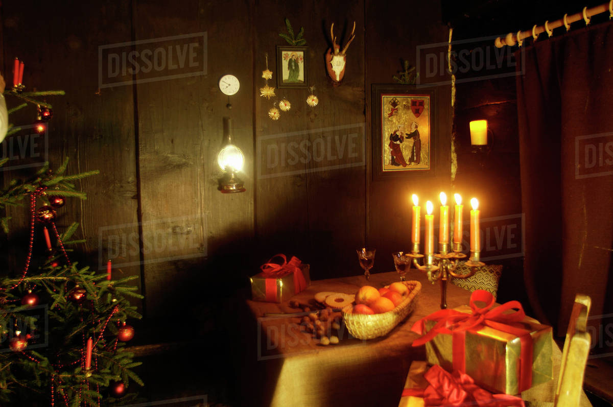 christmas tree and burning candles in alpine hut