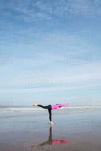 Belgium, Flanders, woman doing yoga exercise on the beach Rights-managed stock photo
