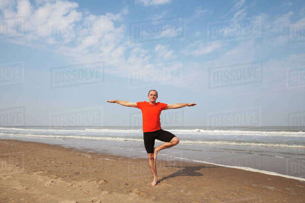 Belgium, Flanders, man doing yoga exercise on the beach Rights-managed stock photo