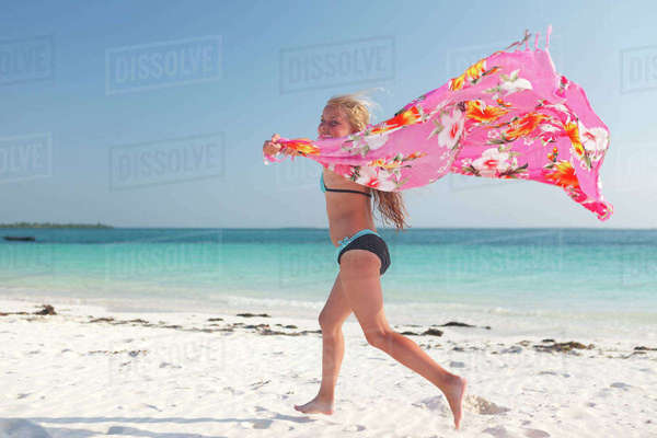 Tanzania, Zanzibar Island, girl with cloth running on the beach at seafront Rights-managed stock photo
