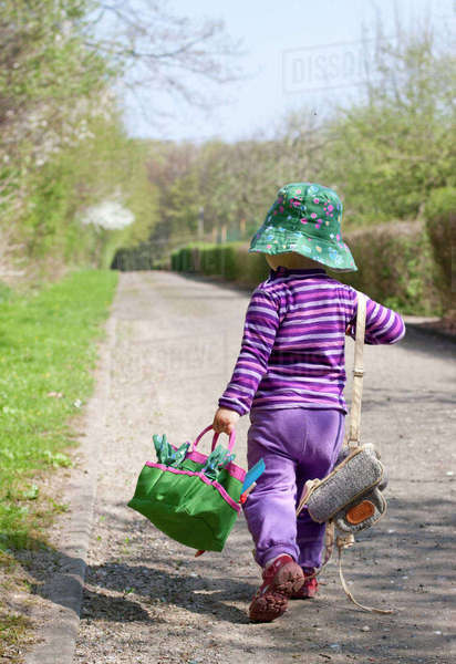 Little girl with hat carrying bags, back view Rights-managed stock photo