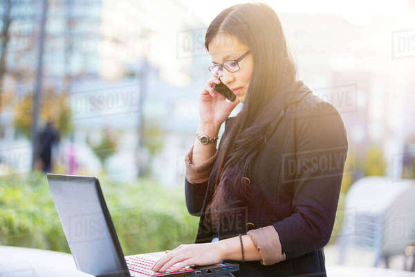 Young businesswoman with laptop telephoning with smartphone Rights-managed stock photo