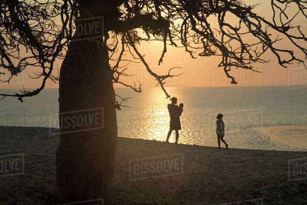 Africa, Madagascar, Woman with children standing at sea at sunset Rights-managed stock photo