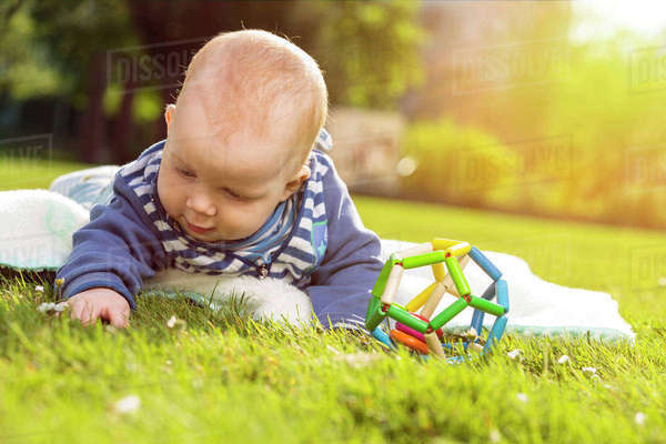 Baby boy lying on a meadow exploring the grass Rights-managed stock photo