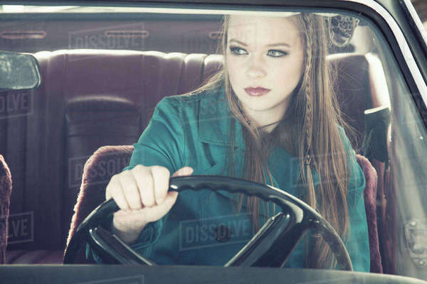 Portrait of young woman at steering wheel of vintage car Rights-managed stock photo