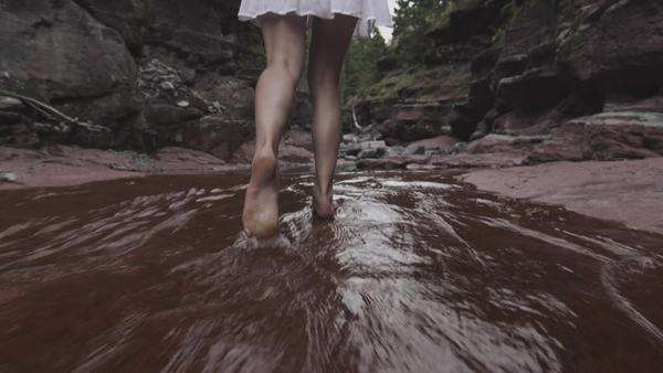 Handheld shot showing the legs of a woman walking through shallow water Royalty-free stock video
