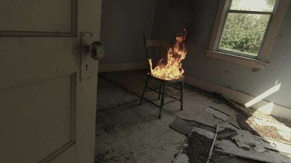 Handheld shot of a burning chair in a crumbling room interior Royalty-free stock video