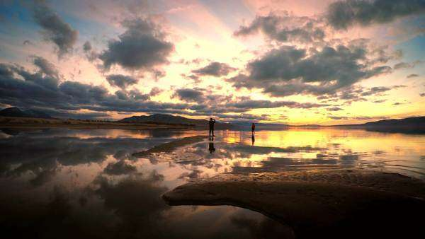 2 people standing on sandbar in Utah Lake during sunset. Royalty-free stock video