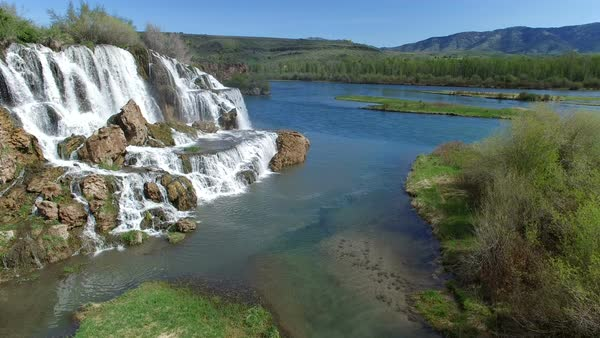 Flying view of waterfall flowing over edge into the Snake River Royalty-free stock video