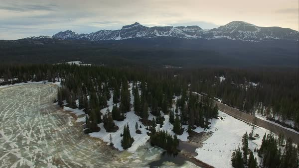 Flying view over a frozen forest in the mountains as snow and ice are slowly melting into Spring. Royalty-free stock video